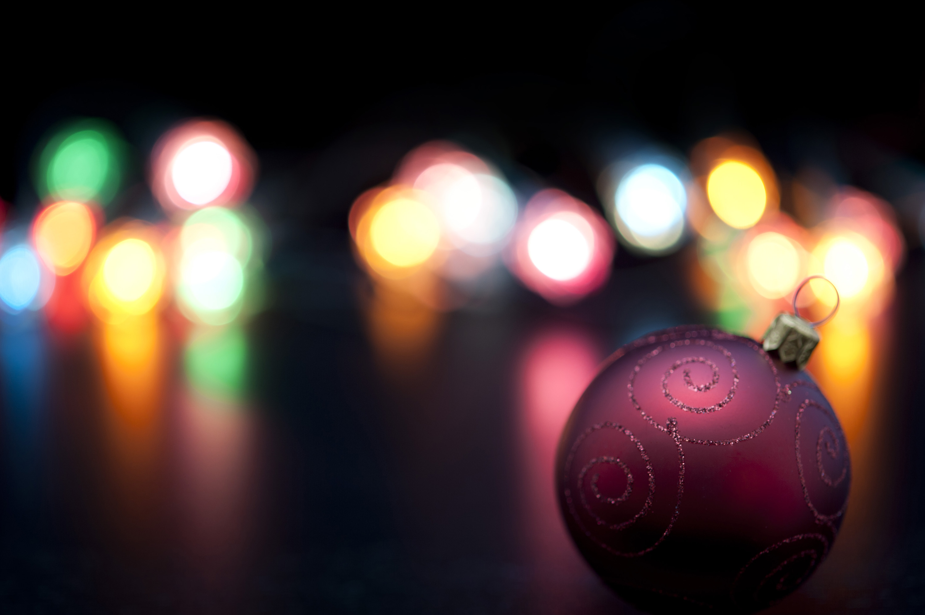Focus to a single decorative maroon Christmas bauble in the foreground with a colourful Christmas lights bokeh backdrop